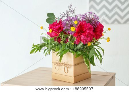 Gift box with beautiful floral composition of different fragrant flowers on table in light room