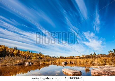Wonderful autumn day. Indian summer in Manitoba, Canada. Cirrus clouds are reflected in the Winnipeg River. Old Pinawa Dam Park. The concept of ecological and recreational tourism