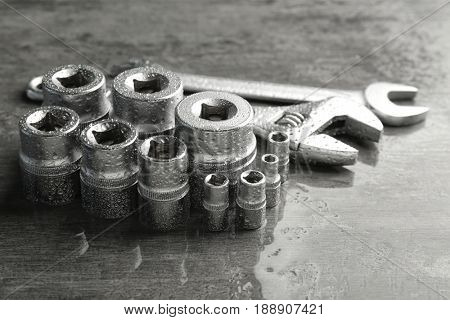 Hand sockets, screw wrench and spanners on wet table