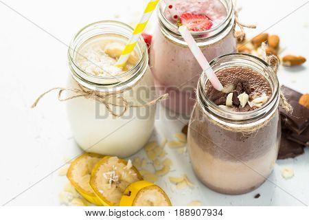 Set of milkshake in jars. Banana chocolate and strawberry milkshakes with nuts and coconut. Summer dessert. Healthy food.