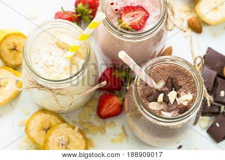 Set of milkshake in jars. Banana chocolate and strawberry milkshakes with nuts and coconut. Healthy food.