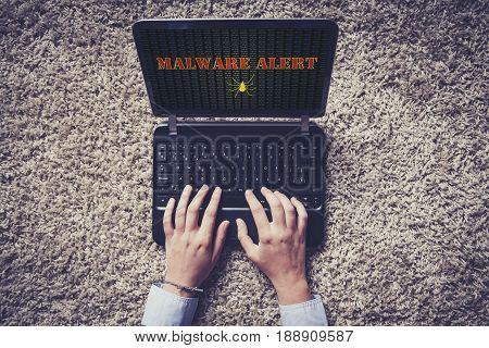 Malware alert in a laptop screen. Top view.