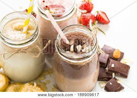 Set of milkshake in jars. Banana chocolate and strawberry milkshakes with nuts and coconut. Summer dessert. Healthy food. Close up.