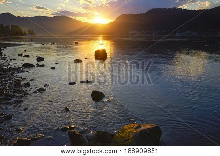 Sunset on the lake on a background of stones in a clear summer day. Warm summer evening on the lake. Fabulous views of the lake in the sunlight Altai