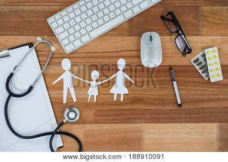 Paper cut out family chain with medicines, mouse, keyboard, stethoscope, clipboard and spectacles on table