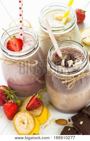 Set of milkshake in jars. Banana chocolate and strawberry milkshakes with nuts and coconut. Summer dessert. Healthy food. Vertical.