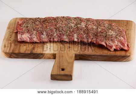 Spices sprinkled on beef ribs against white background