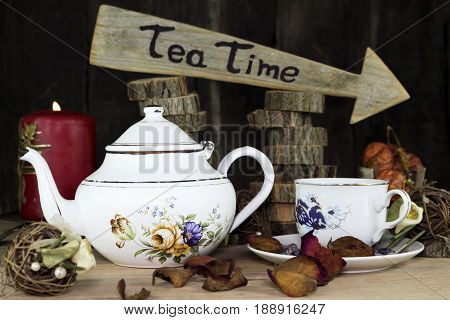 Cup Of Tea And Teapot On Wooden Table. Arrow Sign With Text, Tea Time Written On It In The Backgroun
