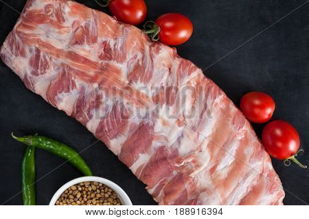 Beef ribs, cherry tomatoes and coriander seeds against black background