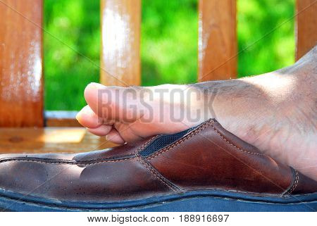 African american male with tired feet from standing at work all day.
