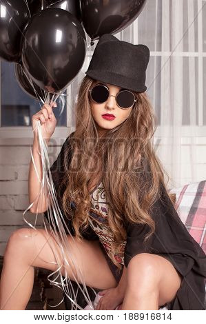 Young attractive woman wearing combination, glasses and bowler-hat posing for camera with a bundle of baloons in her hand.