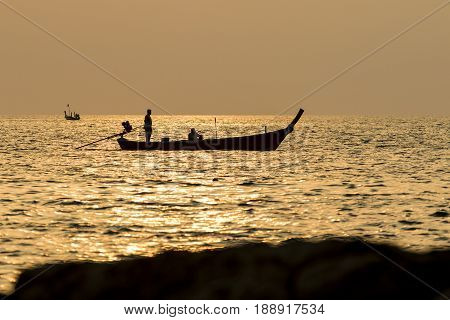 silhouette sunset sky of man on long tail boat phuket thailand