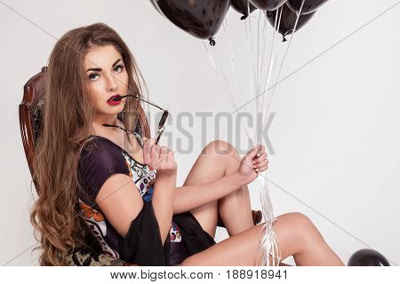 Close-up shot of beautiful girl with long hair and red lips holding a bundle of baloons and glasses in her hands.