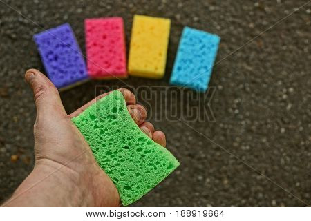 A green sponge in the hand against the background of colored sponges on the floor