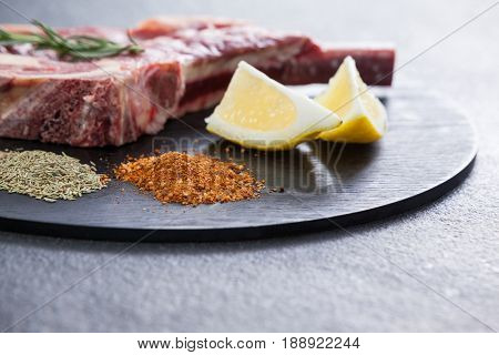 Blade chop, spices and lemon on black round tray against black background