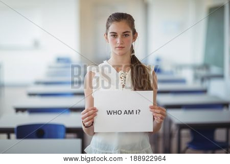 Schoolgirl holding white paper with text sign in classroom at school