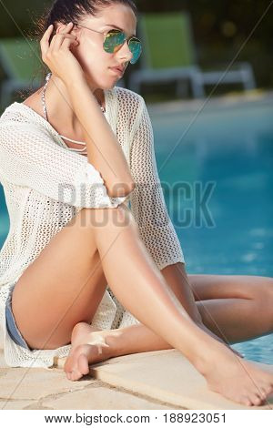 Beautiful young woman sitting by swimming-pool