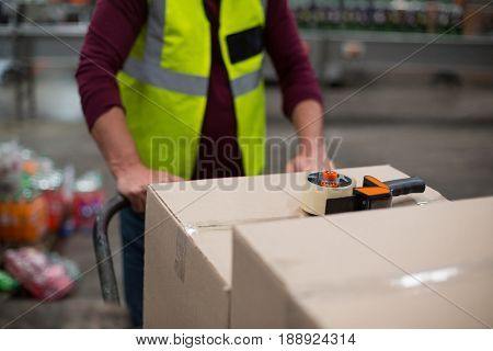 Mid section of factory worker pulling trolley of cardboard boxes in drinks production factory
