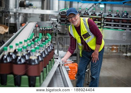 Portrait of factory worker inspecting production line at drinks production factory