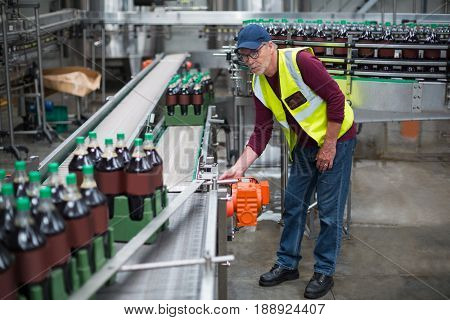 Male factory worker inspecting production line at drinks production factory