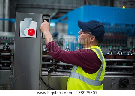 Factory worker operating machine at drinks production factory