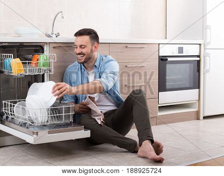 Happy handsome man unloading dishwasher and enjoying in housework. Husband doing chores in kitchen poster
