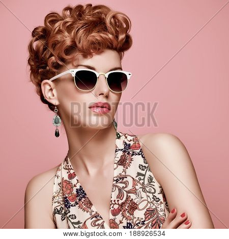Fashion Portrait Model in Sexy Dress. Stylish Mohawk hairstyle, fashion Makeup.Beauty woman in Trendy Sunglasses, Glamour Redhead, fashion pose.Playful Girl, Luxury summer Accessories.Summer Floral Outfit