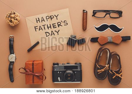 Happy Fathers Day flat lay card with male things and chils shoes on beige background
