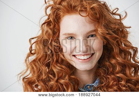 Close up of redhead beautiful natural girl with freckles smiling looking at camera over white background.