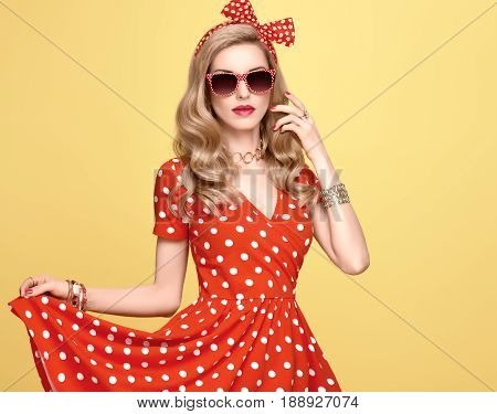 Fashion Model Girl in Polka Dots Summer Dress. Stylish Curly hairstyle, Trendy Clutch, fashion Red Headband, Sunglasses. Beauty Blond Pinup Woman in fashion pose. Glamour Playful Sexy Lady on Yellow
