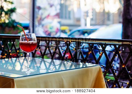 Spanish cold drink from sangria wine in a glass with pieces of fruit and spices on a glass table in a summer cafe photo in blur.