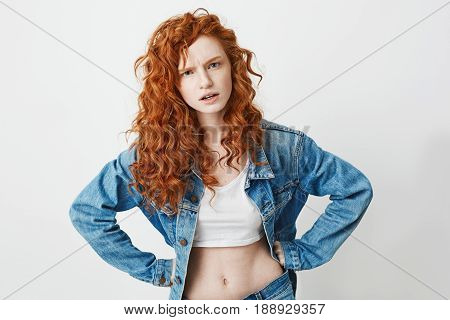 Rude attractive young girl with red curly hair looking at camera brutally with arms akimbo over white background.
