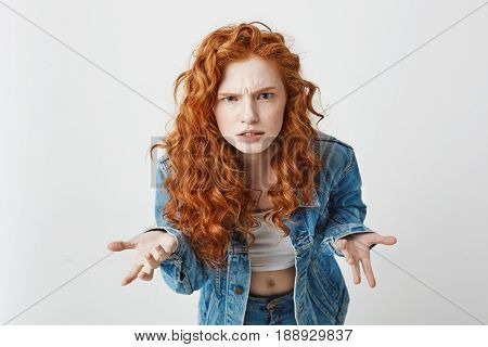 Displeased young foxy girl stretching to camera looking brutally gesturing over white background. Copy space.