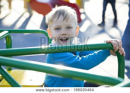 Portrait of a young blonde boy sitting on a carousel at the playground