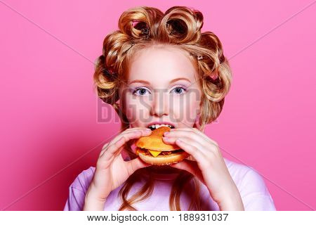 Pretty teen girl with curlers on her hair is eating a hamburger. Pink background. Beauty, fashion concept.