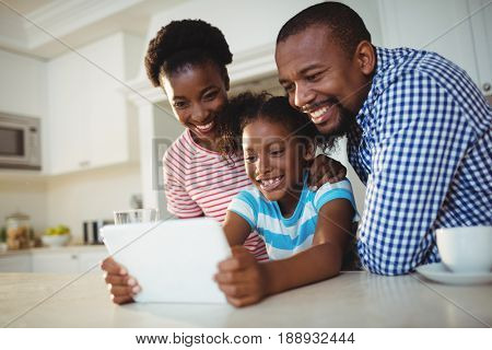 Happy parents and daughter using digital tablet in kitchen at home