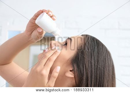 Young woman with bottle of solution for contact lenses, closeup view
