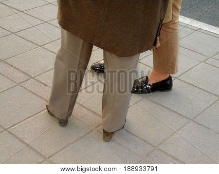 Two women standing on the sidewalk. Only the legs can be see