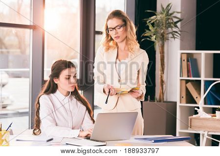 Young Pensive Caucasian Businesswomen In Formalwear Talking While Working At Modern Office