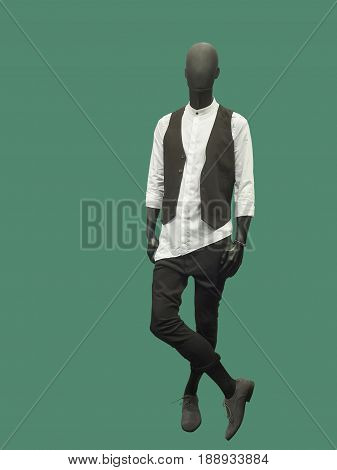 Full-length male mannequin dressed in casual clothes over green isolated. No brand names or copyright objects