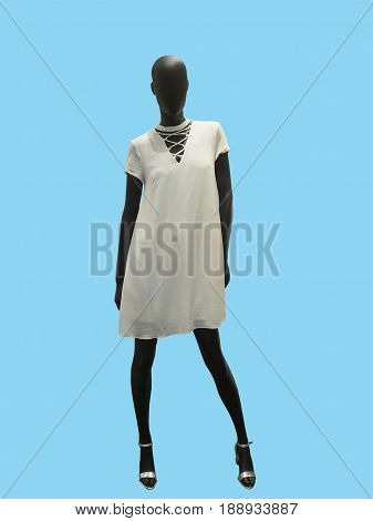 Full-length female mannequin dressed in white dress isolated on blue background. No brand names or copyright objects.