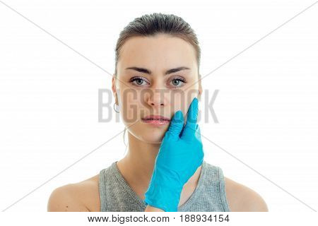 horizontal portrait of a young girl without makeup at a cosmetologist in a blue glove isolated on white background