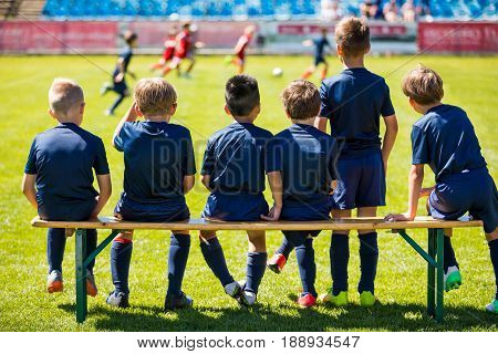 Soccer Match For Children. Young Boys Playing Tournament Soccer Match. Youth Soccer Club Footballers. Young Football Players in Blue Jerseys. Young Soccer Team Sitting on Wooden Bench.