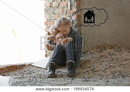 Little girl dreaming about family and home while crying in abandoned building. Poverty concept