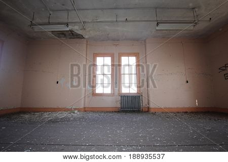 An empty room with a radiator in it.  Part of an old asylum in Michigan