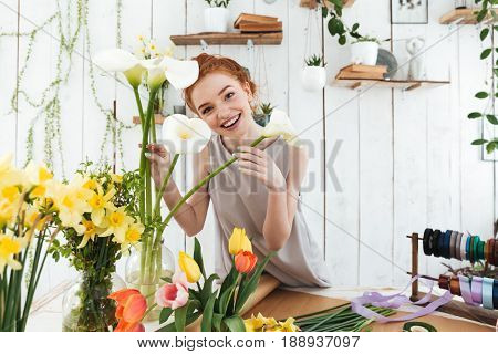 Joyful young lady wearing grey dress looking camera and smiling while holding white callas in workshop