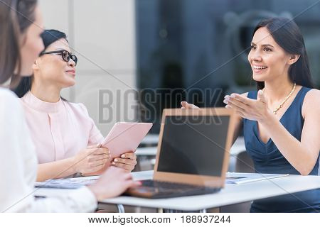 Outgoing business females making conversation with each other while sitting at table and using gadgets. Happy young lady flourishing arms