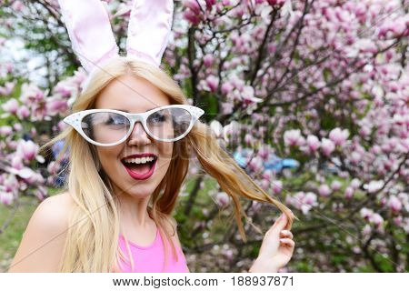 woman or cute girl with funny glasses and bunny ears with long blond hair laughing at blossoming tree with magnolia flowers in spring park on floral environment. Easter. Springtime