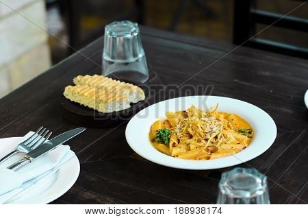 Penne pasta in cream sauce served with shredded cheese on it and grill toasted garlic bread as a side dish.