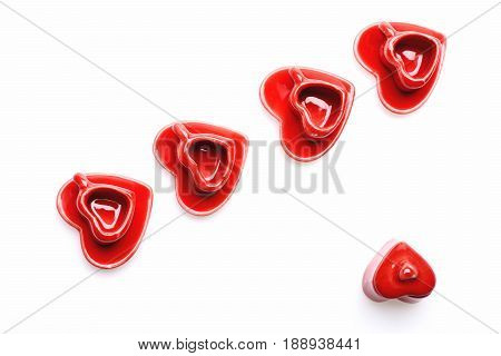 Heart Shaped Saucers And Cups Of Red Colour In Line